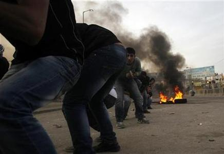 Palestinian stone-throwers duck near burning tyres during clashes with Israeli security forces against Israel's military operation in Gaza, at Qalandia checkpoint near the West Bank city of Ramallah November 16, 2012. REUTERS/Mohamad Torokman
