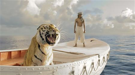 Indian actor Suraj Sharma (R) playing the character Pi, stands near a tiger named Richard Parker in a lifeboat, one of the props used in the new film ''Life of Pi'' by director Ang Lee, in this undated publicity photograph from the film released to Reuters November 16, 2012. REUTERS/Courtesy Fox 2000 Pictures/Gilt Home/Handout