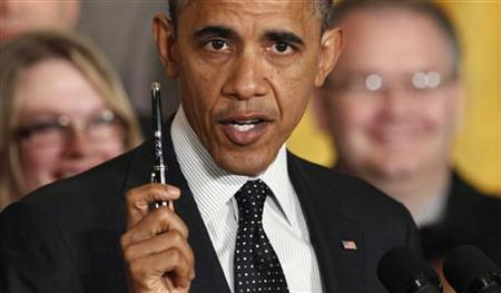 U.S. President Barack Obama holds up a signature pen as he delivers a statement on the U.S. ''fiscal cliff'' in the East Room of the White House in Washington, November 9, 2012. REUTERS/Kevin Lamarque
