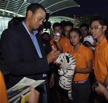 U.S. golfer Tiger Woods (L) sweats as he signs autographs for students from the Singapore Sport School after a coaching session at Marina Bay Sands in Singapore November 1, 2012. REUTERS/Tim Chong