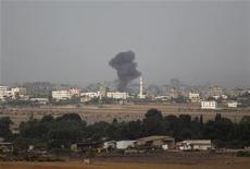 La aviación israelí bombardeaba edificios gubernamentales de Hamás en Gaza el sábado, entre ellos la oficina del primer ministro, después de que el Gabinete israelí autorizara la movilización de hasta 75.000 reservistas, preparándose para una posible invasión terrestre. En la imagen, humo en Ciudad de Gaza tras un ataque israelí, el 17 de noviembre de 2012. REUTERS/Darren Whiteside