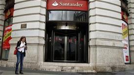 """Un portavoz de Banco Santander confirmó el sábado que la entidad planea invertir en el conocido como """"banco malo"""" que, según fuentes autorizadas del ministerio de Economía, ha de captar antes de fin de año 2.200 millones de euros de inversores privados. En la imagen, una mujer usa un móvil junto a una sucursal de Santander en Madrid, el 25 de octubre de 2012. REUTERS/Sergio Pérez"""