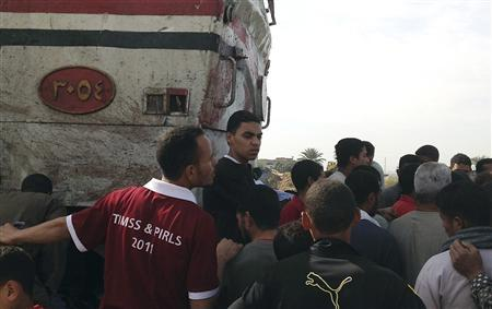 People gather near a train, with bloodstains, after it crashed into a school bus at Manflot in the southern city of Assuit, 500 km (310 miles) south of Cairo, November 17, 2012. REUTERS/Stringer