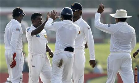 Sri Lanka's Rangana Herath (2nd L) celebrates with teammates after he completed five wickets including taking the wicket of New Zealand's Kruger van Wyk on the first day of their first cricket test match in Galle November 17, 2012. REUTERS/Dinuka Liyanawatte