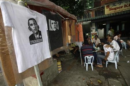 People sit near T-shirts, with an image of U.S. President Barack Obama, displayed at a shop by the streets of Yangon November 17, 2012. REUTERS/Soe Zeya Tun