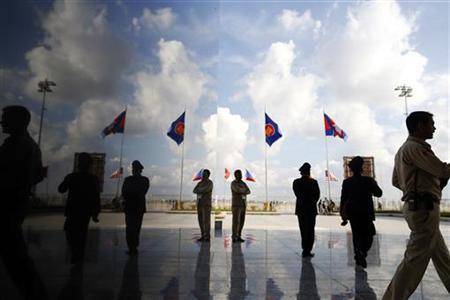 Government security personnel and officials at at the VIP section of Phnom Penh airport are reflected on a marble pillar, as delegations arrive for the 21st ASEAN (Association of Southeast Asian Nations) and East Asia summits November 17, 2012. REUTERS/Damir Sagolj