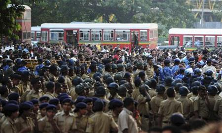 Police officers stand guard in front of a crowd of Shiv Sena supporters gathered near the residence of influential right-wing Hindu nationalist politician Bal Thackeray in Mumbai November 17, 2012. REUTERS/Stringer