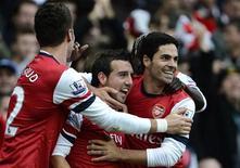 El Arsenal aprovechó despiadadamente un momento de locura de Emmanuel Adebayor para remontar el sábado un emocionante derbi del norte de Londres y derrotar al Tottenham Hotspur por 5-2. En la imagen, Cazorla (centro) y Arteta (derecha) celebran uno de los goles en el partido frente al Tottenham Hotspur. REUTERS/Dylan Martinez