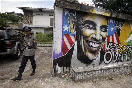 A police officer stands near a graffiti artwork welcoming U.S. President Barack Obama, on a street in Yangon November 17, 2012. Obama will visit Myanmar on November 19. REUTERS/Soe Zeya Tun