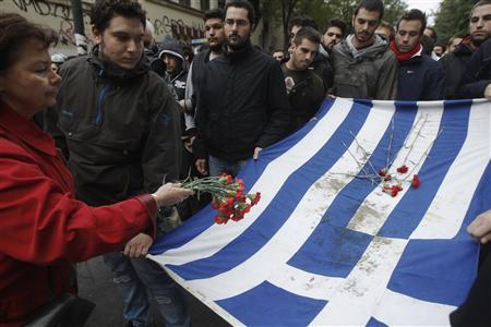Athens' Polytechnic School students carry a blood-stained Greek flag as a woman leaves flowers during a rally marking the anniversary of a 1973 student uprising against a dictatorship then ruling Greece in Athens November 17, 2012. Thousands of austerity-hit Greeks marched to the U.S. embassy to mark the bloody uprising against the military junta that ruled Greece. REUTERS/John Kolesidis