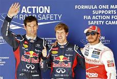 Red Bull Formula One driver Sebastian Vettel of Germany (C) gives a thumbs-up next to team mate Mark Webber (L) of Australia and McLaren Formula One driver Lewis Hamilton (R) of Britain following the qualifying session of the U.S. F1 Grand Prix at the Circuit of the Americas in Austin, Texas November 17, 2012. Vettel will start the U.S. Grand Prix from pole position on Sunday, with Hamilton alongside on the front row and Webber third on the starting grid. REUTERS/Jim Young