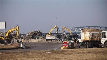 Garbage trucks wait to enter the parking lot at Jacob Riis Park, which has been converted temporarily into a landfill to accommodate all the debris and garbage created by Hurricane Sandy, in the Neponsit neighborhood of Queens, New York in this November 11, 2012 file photo.The temporary garbage dump at Jacob Riis Park in Queens is one of several sites around the city. REUTERS/Andrew Burton