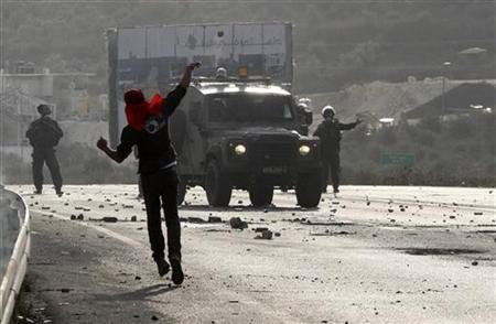 A Palestinian protester throws a stone at Israeli security forces during clashes against Israel's military operation in the Gaza Strip, at Hawara checkpoint near the West Bank city of Nablus November 17, 2012. REUTERS/Abed Omar Qusini