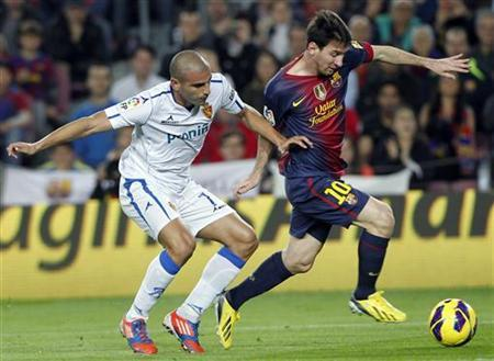 Barcelona's Lionel Messi (R) eludes Zaragoza's Carlos Aranda during their Spanish First Division soccer league match at Camp Nou stadium in Barcelona November 17, 2012. REUTERS/Albert Gea
