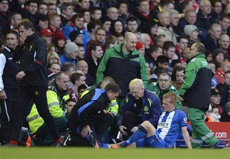 Wigan Athletic's Ben Watson (R) is treated for a broken leg during their English Premier League soccer match against Liverpool in Liverpool, northern England November 17, 2012. REUTERS/Nigel Roddis