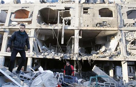 Palestinians inspect a destroyed house after an Israeli air strike in Gaza City November 18, 2012. REUTERS-Ahmed Zakot