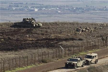 An Israeli military vehicle tows another as a tank stands in position close to the ceasefire line between Israel and Syria on the Israeli-occupied Golan Heights November 13, 2012. REUTERS/Nir Elias