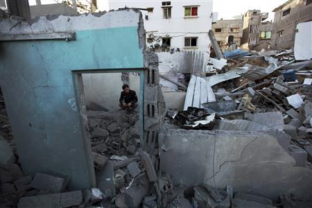 A Palestinian man sits amongst the rubble of a destroyed house after an Israeli air strike in the northern Gaza Strip November 18, 2012. REUTERS-Mohammed Salem