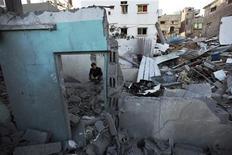 Israel bombardeó objetivos milicianos palestinos en la Franja de Gaza el domingo por quinto día consecutivo, preparándose para una posible invasión terrestre mientras desgranaba sus condiciones para una tregua. En la imagen, un palestino se sienta sobre los escombros de una casa destruida en la Franja de Gaza, el 18 de noviembre de 2012. REUTERS/Mohammed Salem