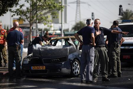 Israeli police explosives experts stand near a vehicle damaged from falling debris after a rocket was shot down by Iron Dome air shield just outside Tel Aviv November 18, 2012. REUTERS/Daniel Bar-On