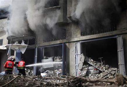 Palestinian firefighters extinguish a fire after an Israeli air strike on a house in Gaza City November 18, 2012. REUTERS-Ahmed Jadallah