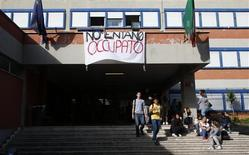 """Students are seen at the entrance of Nomentano Science school in Rome, November 13, 2012. Nomentano Science School this week became the latest in over a dozen schools around Rome to be seized by their students in a protest against reforms and cuts imposed by the technocrat government of Mario Monti in an attempt to pull Italy out of financial crisis. The banner reads, """"Nomentano occupied"""". REUTERS/Max Rossi"""