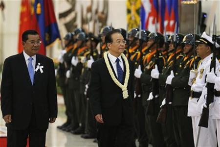 Cambodia's Prime Minister Hun Sen (L) accompanies Chinese Premier Wen Jiabao as he inspects honor guards after he arrived for the 21st ASEAN (Association of Southeast Asian Nations) and East Asia summits in Phnom Penh November 18, 2012. REUTERS/Damir Sagolj