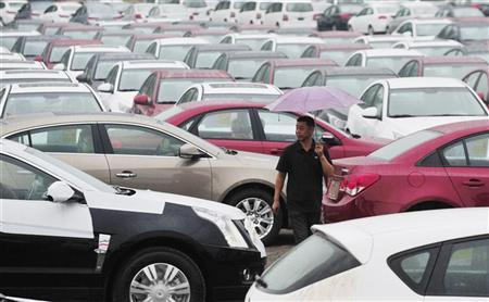 An employee walks past new cars at a General Motors parking lot in Shenyang, Liaoning province August 1, 2012. REUTERS/Stringer