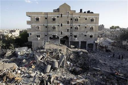 Palestinians inspect a destroyed house after an Israeli air strike in Rafah in southern Gaza Strip November 18, 2012. REUTERS/Ibrahemm Abu Mustafa