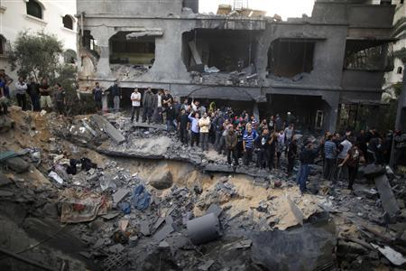 Palestinians gather around a destroyed house after an Israeli air strike in Gaza City November 18, 2012. REUTERS/Suhaib Salem