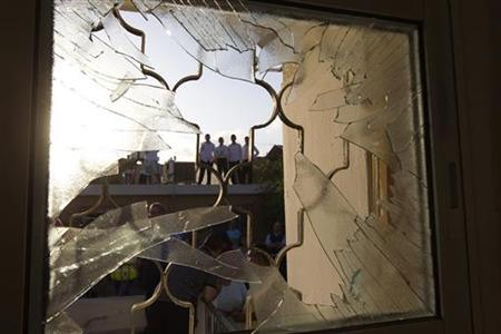 Israelis are seen through a window damaged after a rocket fired from the Gaza Strip landed in the southern town of Ofakim November 18, 2012. Israel bombed Palestinian militant targets in the Gaza Strip from air and sea for a fifth straight day on Sunday, preparing for a possible ground invasion while also spelling out its conditions for a truce. REUTERS/Ronen Zvulun