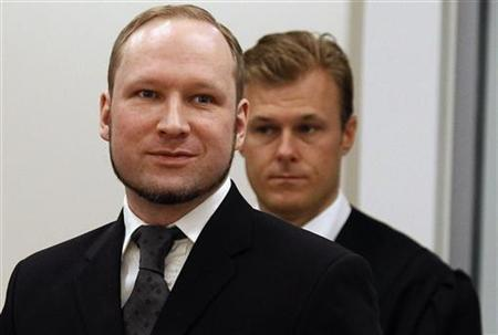 Norwegian mass killer Anders Behring Breivik (L) smiles as he arrives at the court room in Oslo Courthouse August 24, 2012. REUTERS/Stoyan Nenov