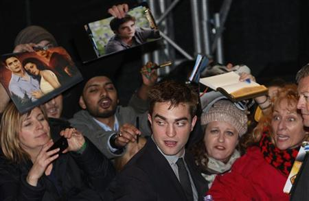 Actor Robert Pattinson signs autographs for fans as he arrives for the European premiere of ''The Twilight Saga: Breaking Dawn Part 2'' in London November 14, 2012. REUTERS/Suzanne Plunkett