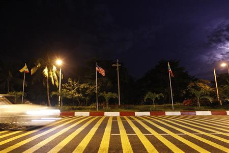 Cars pass along a road to Yangon Air Port where U.S and Myanmar flags are posted in Yangon November 18, 2012. U.S. President Barack Obama said on Sunday that his upcoming trip to Myanmar was not an endorsement of the government, but rather an acknowledgement of the progress it has made in moving towards democracy after decades of military rule. REUTERS/Minzayar