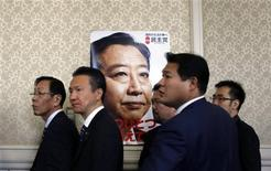 Members of the ruling Democratic Party of Japan stand next to a poster of Japanese Prime Minister Yoshihiko Noda after a meeting at the parliament in Tokyo in this November 15, 2012 file photo. Japan ruling party lawmaker Mieko Nakabayashi isn't just worried that her Democratic Party will lose power in next month's election; she fears a comeback by rival conservative Liberal Democrats will spell a return to the prolonged one-party rule that critics blame for many of the country's past policy ills. Three years after the Democratic Party of Japan (DPJ) ended more than half a century of nearly non-stop Liberal Democratic Party (LDP) rule, surveys suggest disappointed voters will hand the LDP the most seats in a December 16 poll for parliament's lower house. That would put LDP leader Shinzo Abe in pole position to form the next government and regain a job he quit in 2007. REUTERS/Yuriko Nakao