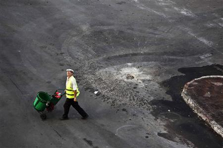 A municipality worker walks past a hole in the road after a rocket fired by Palestinian militants in Gaza landed in the southern city of Ashdod November 18, 2012. REUTERS/Nir Elias
