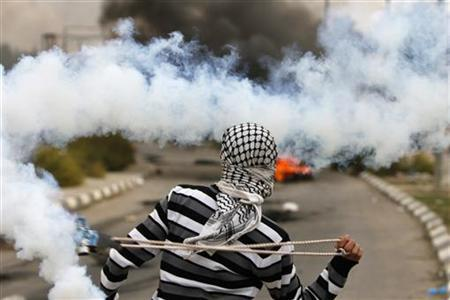 A Palestinian stone-thrower uses a sling to throw back a tear gas canister fired by Israeli security forces during clashes outside Ofer prison near the West Bank city of Ramallah November 18, 2012. The clashes broke out following a protest against Israel's military operation in the Gaza Strip. REUTERS/Mohamad Torokman