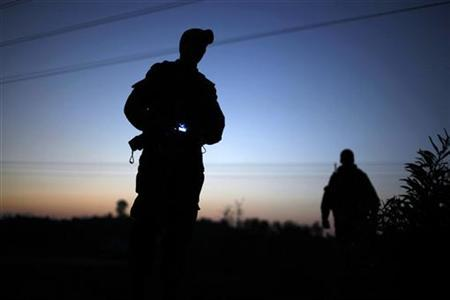 An Israeli soldier stands on the side of the road near the border with the Gaza Strip November 18, 2012. REUTERS/Amir Cohen