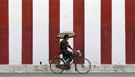A woman rides her bicycle on a road in Jaffna September 10, 2012. REUTERS/Dinuka Liyanawatte