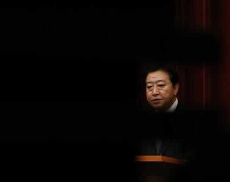 Japan's Prime Minister Yoshihiko Noda is seen through a silhouette of a decoration on a wall during his news conference at his official residence in Tokyo November 16, 2012. REUTERS/Kim Kyung-Hoon