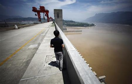 A man stands on the Three Gorges dam in Yichang, Hubei province August 9, 2012. REUTERS/Carlos Barria/Files