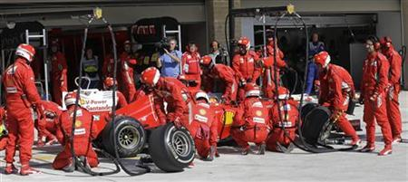 Pit crew perform a pit stop on the car of Ferrari Formula One driver Fernando Alonso of Spain during the U.S. F1 Grand Prix at the Circuit of the Americas in Austin, Texas November 18, 2012. REUTERS/Luca Bruno/Pool