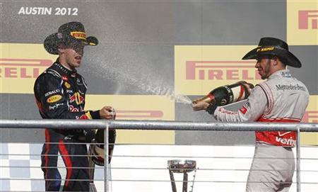 McLaren Formula One driver Lewis Hamilton (R) of Britain and Red Bull Formula One driver Sebastian Vettel of Germany spray champagne during the podium ceremony after the U.S. F1 Grand Prix at the Circuit of the Americas in Austin, Texas November 18, 2012. REUTERS/Adrees Latif