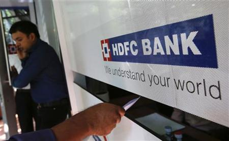 A customer walks out of a HDFC Bank branch as another deposits a cheque at a counter in Mumbai November 17, 2012. REUTERS/Vivek Prakash
