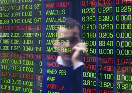 An office worker talks on his phone as he looks the stock board at the Australian Securities Exchange (ASX) building in central Sydney June 15, 2012. REUTERS/Daniel Munoz