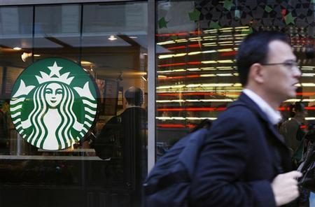 A pedestrian walks past the new Starbucks logo on a store in Times Square in New York March 8, 2011. REUTERS/Lucas Jackson/Files
