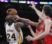 Los Angeles Lakers shooting guard Kobe Bryant (24) battles Houston Rockets small forward Chandler Parsons (C) and Rockets center Omer Asik (R) for the ball during the second half of their NBA basketball game in Los Angeles, California November 18, 2012. Lakers won the game 119-108 with Bryant scoring a triple-double, 22 points, 11 rebounds and 11 assists. REUTERS/Alex Gallardo