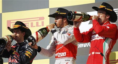 McLaren Formula One driver Lewis Hamilton of Britain, Red Bull Formula One driver Sebastian Vettel (L) of Germany and Ferrari Formula One driver Fernando Alonso (R) of Spain drink champagne during the podium ceremony after the U.S. F1 Grand Prix at the Circuit of the Americas in Austin, Texas November 18, 2012. Hamilton won the U.S. Grand Prix on Sunday while championship leader Vettel failed to clinch his third consecutive drivers' title on his 100th career start. Alonso came in third. REUTERS/Robert Galbraith