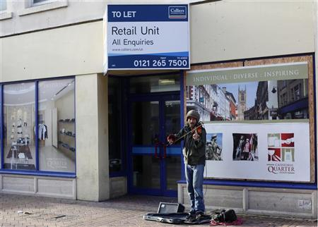 A busker performs in front of an empty retail unit in Derby, central England, December 9, 2011. REUTERS/Darren Staples