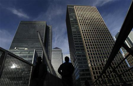 Silhouetted workers walk in front of office towers in the Canary Wharf financial district in London February 16, 2011. REUTERS/Luke MacGregor